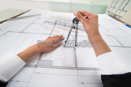 architect hands using compass over blueprint