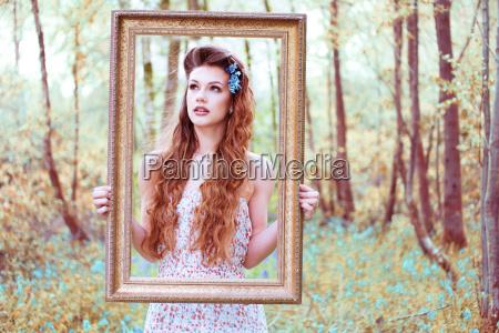 hinreissend frau schaut durch ein portraetrahmen