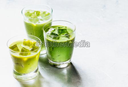 gesunde gruene smoothie shakes in trinkglaeser