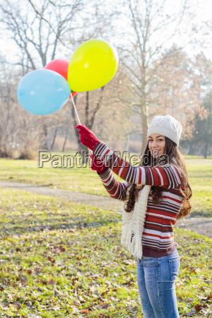 glueckliche junge frau mit bunten luftballons