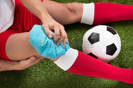fussballspieler icing knee mit eisbeutel