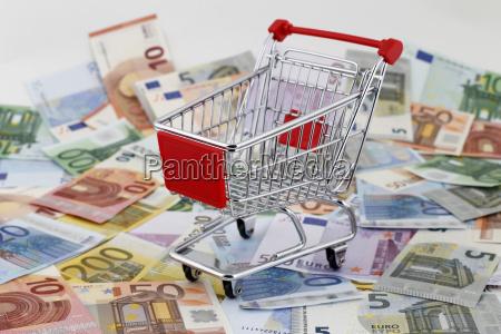 roter einkaufswagen auf euro scheinen