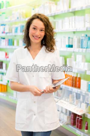 attraktive apotheker mit tablet bei der