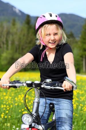 froehliches maedchen mit fahrrad