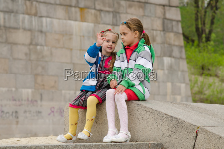 girl shows something other girl sitting