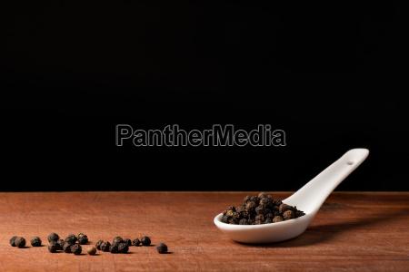 schwarze pfeffer koerner auf porzelan loeffel