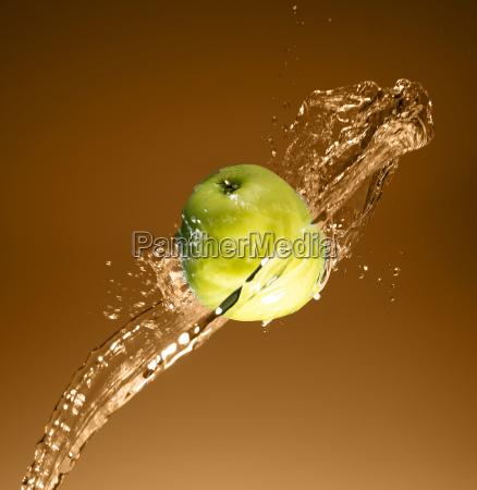 gruener apfel mit wasserspritzen auf beige