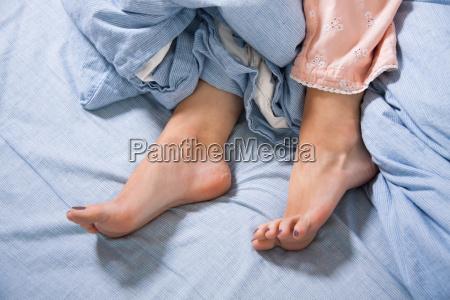 weibliche fuesse mit schlafanzug im bett