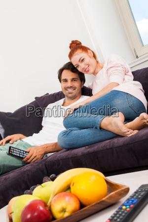 junges liebespaar sitzt im wohnzimmer auf