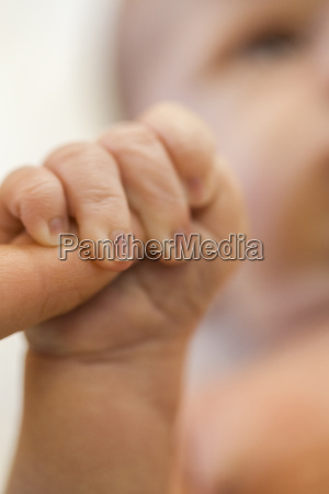 neugeborenes baby greift den finger der