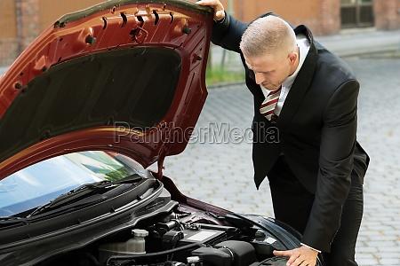man watching the motor eines autos