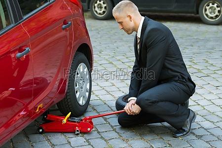 man using red hydraulic floor jack