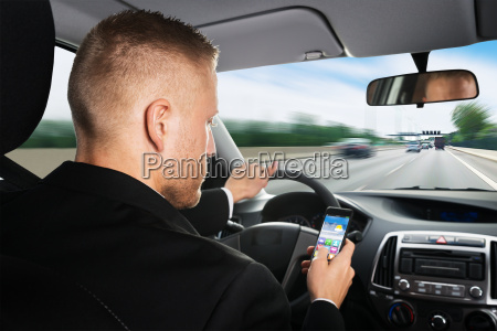 businessman using cellphone while driving a