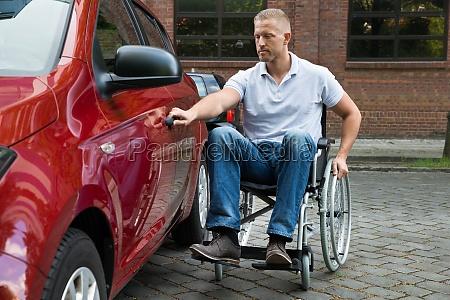 handicapped man opening door of a