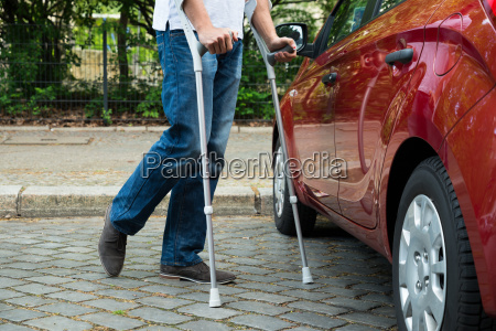 disabled man with crutches walking near