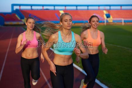 athleten gruppe laeuft auf leichtathletik rennstrecke