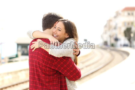 paar umarmt gluecklich in einem bahnhof