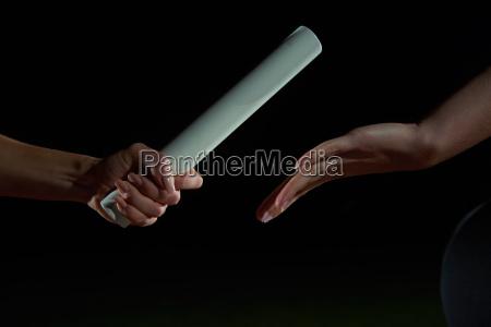 athletischen laeufer staffelstab in staffellauf vorbei
