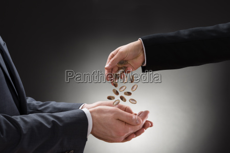 businessman pouring coins on colleagues hand