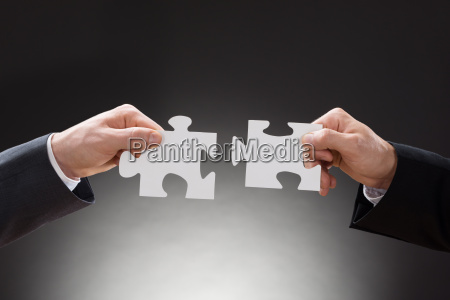 zwei geschaeftsleute halten puzzleteile