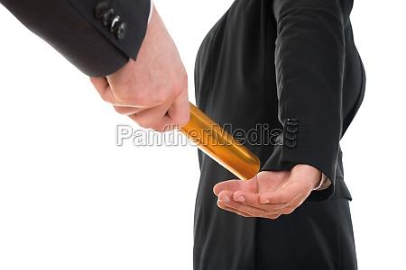 person passing a golden relay baton
