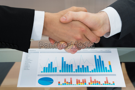 businesspeople shaking hand in front of