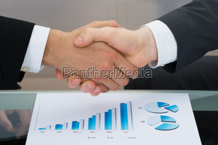 businessmen shaking hand in front of