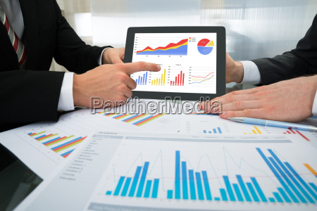 two businessman discussing graph on digital