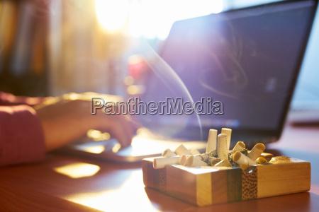 man using laptop and smoking cigarette