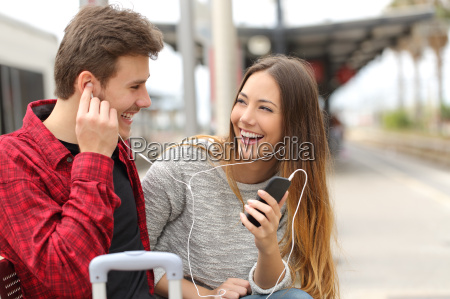 happy couple of travelers sharing music