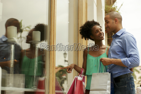 african american couple look shop window