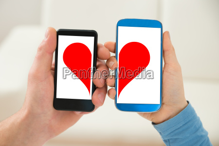 couple holding cellphone with half heart