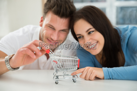 smiling couple looking at miniature shopping