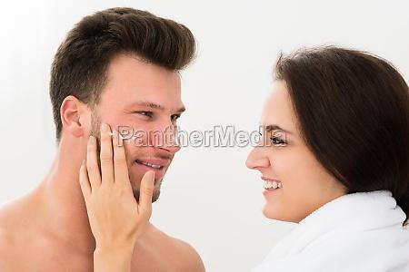 woman applying moisturizer on mans cheek