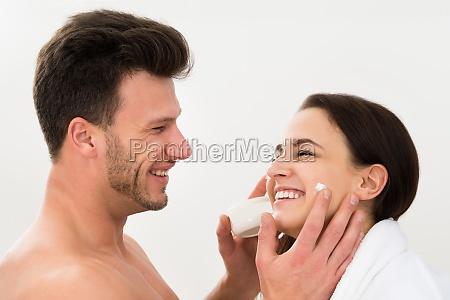man applying moisturizer on womans cheek