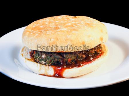 nahaufnahme eines saftigen hamburger zwischen broetchen