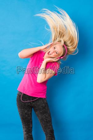 junge blonde frau hoert musik und