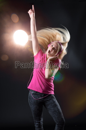 young woman in stage lighting rocks