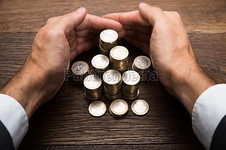 hand des geschaeftsmannes schutz euro muenzen