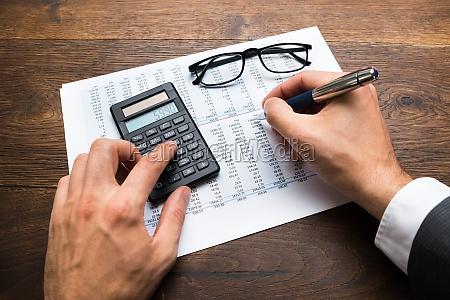 businessman calculating financial sheet