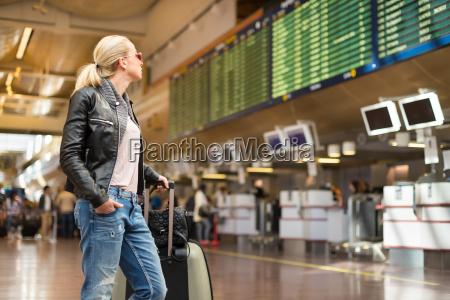 viajero femenino comprobando salidas de vuelo