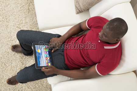 man sitting on couch using digital