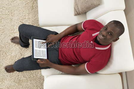 man sitting on couch holding digital