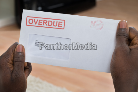 person holding overdue notice