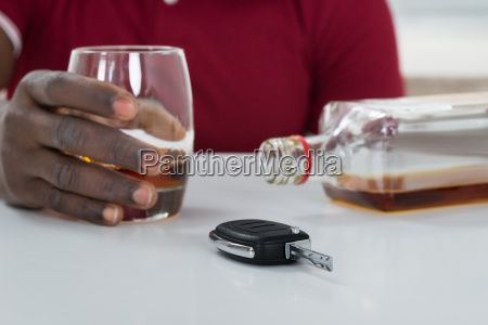 man with car key consuming alcohol