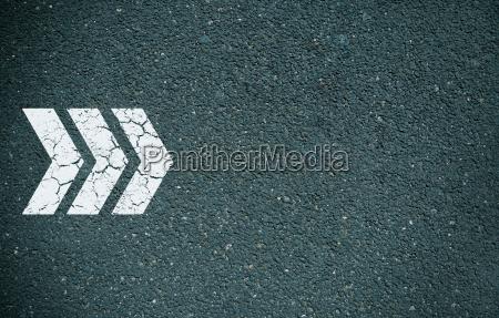 pfeil vorwaerts auf asphalt