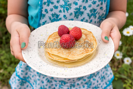 a girl holding a plate of