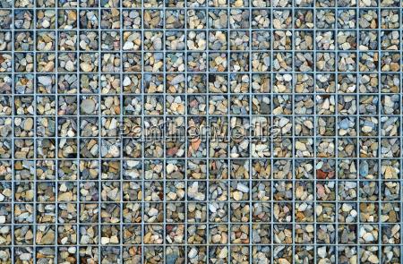 kleine kieselsteine zwischen metallgitter