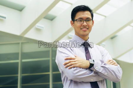 portrait chinese businessman smiling outside office