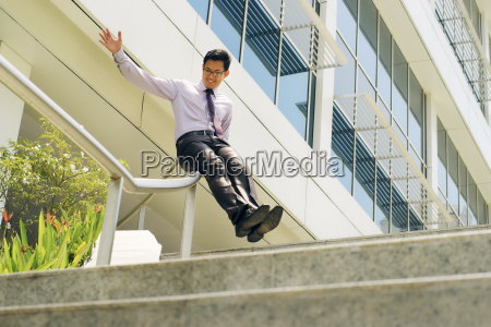 chinese businessman going downstairs sliding on